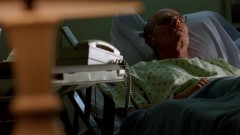 Walt lies in his hospital bed.