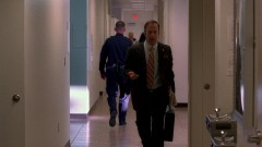 Saul is walking through the police station.