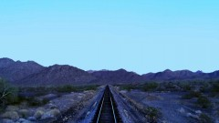 A train drives through the desert.