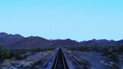 A train drives through the desert.